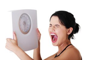 Woman Holding Scale because of healthy foods that can make you fat - Surprising Foods