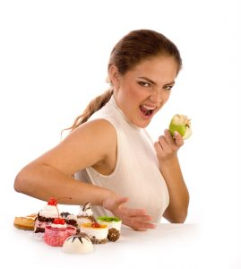 Photo - Woman eating apple instead of desserts